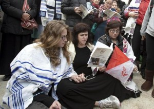 Susan Silverman, center, a reform rabbi, sits on the ground and prays with her daughter, left, after being asked by Israeli police to remove their prayer shawls at the Western Wall in Jerusalem's Old City February 11, 2013. (STRINGER, REUTERS / February 11, 2013)