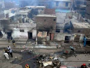 Pakistani police officials examine the burnt out houses of members of the Christian community in Lahore / AFP/Getty Images, via The Independent