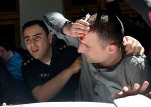 A police officer helped an injured man. Gay rights marchers said priests from the Georgian Orthodox Church led the charge past police cordons. Reuters photo, via the New York Times.