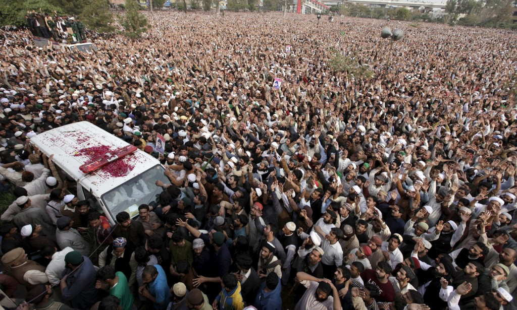 People crowd around the ambulance carrying the body of Mumtaz Qadri during his funeral in Rawalpindi. Photograph: Faisal Mahmood/Reuters, via The Guardian