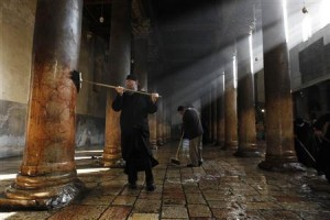 A member from the Greek Orthodox clergy (L) and a Palestinian use diesel to scrub the floor and columns of the Church of the Nativity, the site revered as the birthplace of Jesus, in the West Bank town of Bethlehem December 28, 2011. REUTERS/Ammar Awad