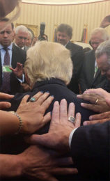 Evangelical supporters place hands on and pray with President Trump in the Oval Office of the White House. Photo courtesy of Johnnie Moore / via Religion News Service