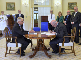 In this photo provided by the Australian Government Royal Commission, Commissioner Justice Peter McClellan, seated left, watches as Governor-General of Australia Peter Cosgrove, seated right, signs a document after receiving the final report of the Royal Commission into Institutional Responses to Child Sexual Abuse at Government House, in Canberra, Dec. 15, 2017. The commission delivered its final 17-volume report and 189 recommendations following a wide-ranging investigation. (Jeremy Piper/Australian Government Royal Commission via AP)